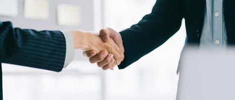 due giovani uomini d'affari asiatici si stringono la mano dopo aver firmato un contratto foto