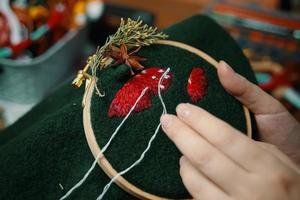 le mani della donna che cuciono sul panno verde. foto