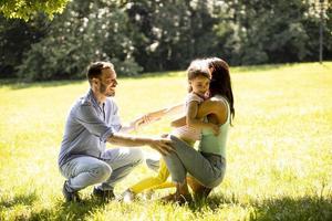 giovane famiglia felice con la piccola figlia carina che si diverte nel parco in una giornata di sole foto