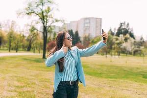 allegra giovane donna in abito blu che cammina nel parco e si fa selfie con lo smartphone e mostra il pollice all'aperto foto