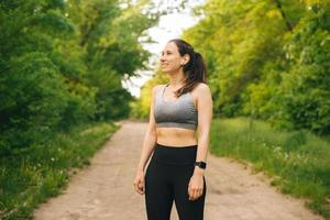 Ritratto di giovane donna sportiva che indossa abbigliamento sportivo all'aperto nel parco durante il tramonto foto