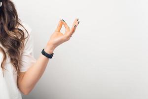 foto ravvicinata della mano di una donna che fa un gesto zen