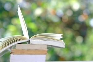 libro sul tavolo di legno e apprendimento dell'istruzione in biblioteca, pila di pile di libri sul tavolo e concetto di idea foto