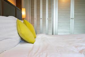 comoda decorazione del cuscino sul letto nella camera da letto dell'hotel foto