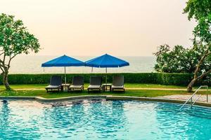 sedie a sdraio o lettini con ombrelloni intorno alla piscina all'ora del tramonto foto