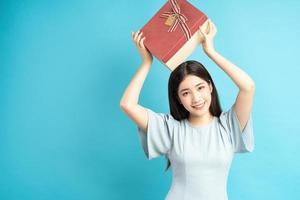 donna asiatica che tiene scatola regalo foto