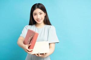 donna asiatica che tiene scatole regalo foto