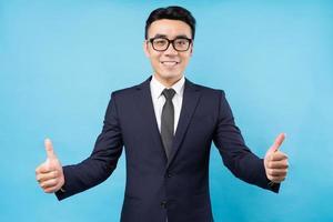 uomo d'affari asiatico che dà i pollici in su su sfondo blu foto
