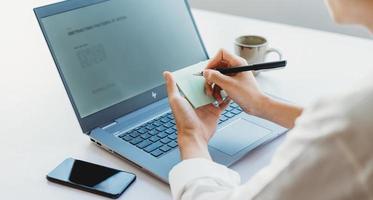 donna d'affari asiatica che annota informazioni dallo schermo del laptop foto