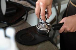 una lavoratrice usa un tamper per premere i chicchi di caffè tostato prima che vengano messi nella macchina del caffè foto