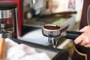 una lavoratrice preme i chicchi di caffè finemente macinati contro un tamper foto
