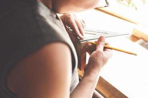un falegname misura i piatti per assemblare le parti. e costruire un tavolo di legno per i clienti. foto