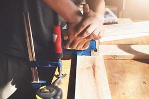 falegnameria dell'imprenditore che tiene una graffatrice per assemblare i pezzi di legno come ordinato dal cliente. foto