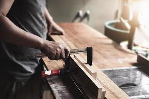 gli operatori della lavorazione del legno stanno decorando pezzi di legno per assemblare e costruire tavoli in legno per il cliente foto