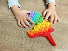 un bambino gioca con un giocattolo pop it foto