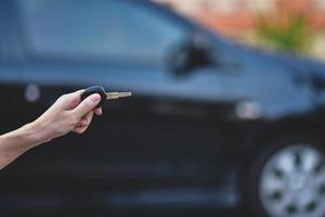 mano che tiene la chiave e l'auto parcheggiata sullo sfondo foto