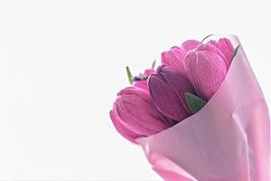 un mazzo di fiori di carta ondulata colorata a forma di tulipani con dentro una caramella. regalo, un segno di attenzione per una vacanza, un compleanno. foto