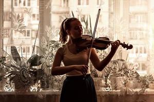 sagoma di una giovane ragazza, un musicista. suonare il violino in sottofondo alla finestra foto