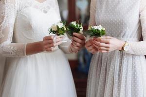 bellissimo boutonier da sposa con fiori bianchi e verdi nelle mani della sposa e delle amiche in abito bianco foto