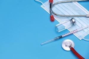 bottiglia medica, fiala, siringa, stetoscopio e maschera facciale su sfondo blu con spazio di copia. sessione di vaccinazione e miglioramento dell'immunità. foto