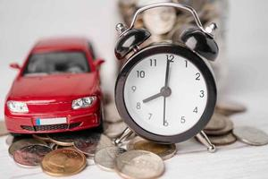 auto e sveglia su monete, prestito auto, finanza, risparmio di denaro, assicurazioni e concetti di tempo di leasing. foto
