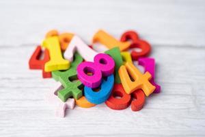 numero di matematica colorato su sfondo di legno, concetto di insegnamento dell'apprendimento della matematica dello studio dell'istruzione. foto