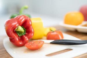 peperone rosso dolce e pomodoro con coltello sul tagliere, insalata di verdure, cucinare cibo sano foto