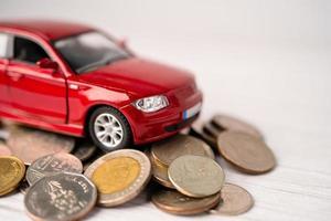 auto su sfondo di monete, prestito auto, finanza, risparmio di denaro, assicurazione e concetti di tempo di leasing. foto