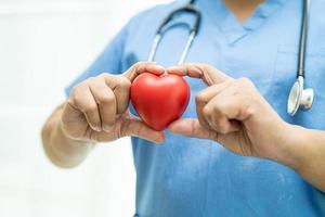 paziente asiatico anziana o anziana donna anziana che tiene il cuore rosso in mano sul letto nel reparto ospedaliero di cura, concetto medico sano e forte foto