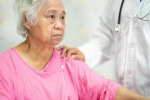 medico asiatico che tocca paziente asiatico anziana o anziana donna anziana con amore, cura, aiuto, incoraggiamento ed empatia nel reparto ospedaliero di cura, concetto medico sano e forte. foto