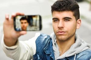 selfie di giovane uomo in fondo urbano con uno smartphone foto