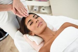 donna che riceve massaggio alla testa nel centro benessere spa. foto