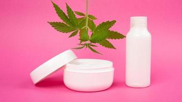 cosmetici per la cura della pelle con estratto di marijuana su sfondo rosa, crema ringiovanente con foglia di cannabis foto