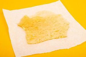 estratto di cera di marijuana ad alto thc su carta pergamena su fondo giallo foto