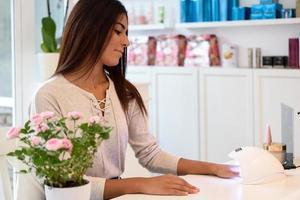 donna che utilizza unghie curate nella lampada uv. foto