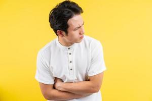 uomo asiatico che ha mal di stomaco su sfondo blu foto