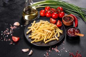 patatine fritte calde fresche con verdure salate e spezie foto