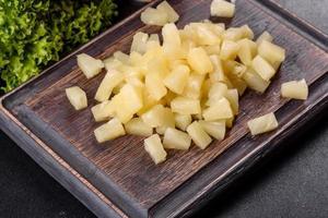 ananas in scatola con pezzi su un tagliere di legno foto