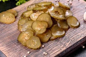 gustoso cetriolo sottaceto piccante salato tagliato con anelli su un tagliere di legno foto