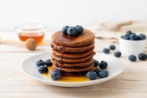 pila di pancake al cioccolato con mirtillo e miele su un piatto foto