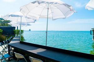 bar all'aperto vuoto e sedie con sfondo di mare foto