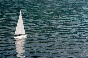 modello di barca a vela bianca che galleggia nel lago. foto