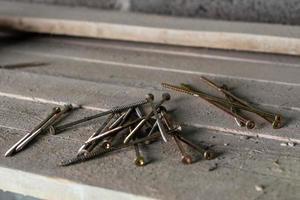 viti per legno adagiate sulle assi di legno allentate. foto