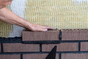 muratore operaio che installa mattoni in cantiere. foto