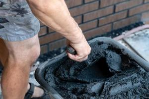 la mano dell'uomo tiene una cazzuola e un cemento misto nel secchio. foto