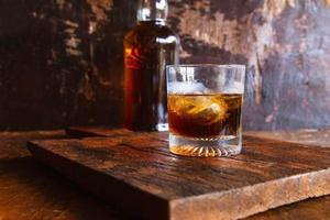 bicchiere da liquore e decanter su tavola di legno foto