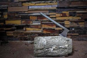 la vecchia ascia di metallo con l'incastrato in un tronco alle pareti è fatta di diversi tipi di sfondo di struttura di legno foto