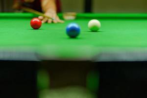 il giocatore stava tirando la palla sul tavolo da biliardo verde foto