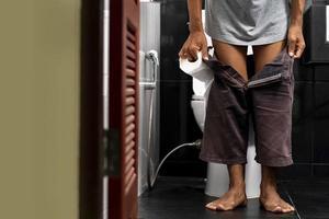 uomo che tiene in mano un rotolo di carta igienica nella toilette di casa sua foto