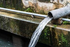 flusso di acque reflue alla fogna, tubi di fognatura al piccolo canale foto
